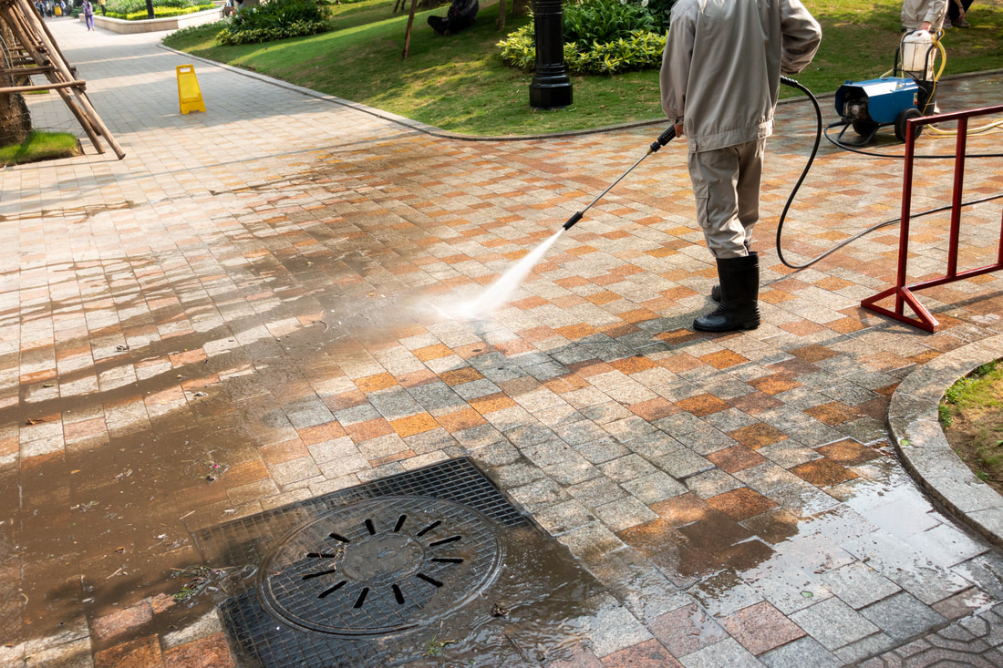 Block paving being jet washed and cleaned by worker