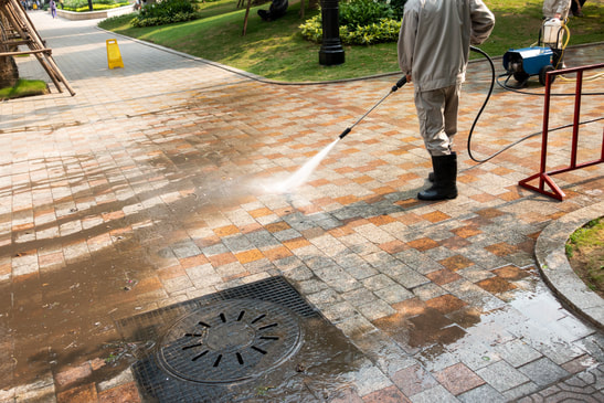 Man jet washing block paved driveway with standard lance