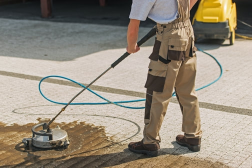 Man cleaning block paved driveway with rotary jet cleaning device