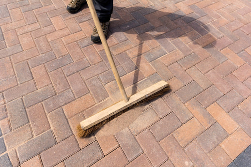Worker sweeping in dry kiln sand into block paved driveway to seal joints for strengthening purposes